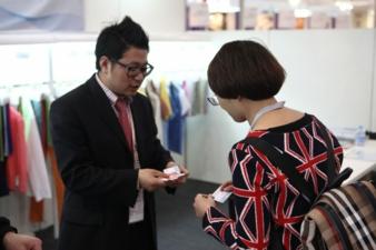 Visitenkarten werden immer rege ausgetauscht. Blick auf einen asiatischen Messestand